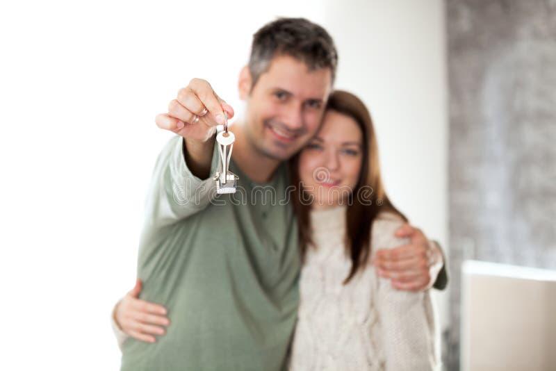 Glückliche junge Paare, die in ein neues Haus sich bewegen lizenzfreies stockbild