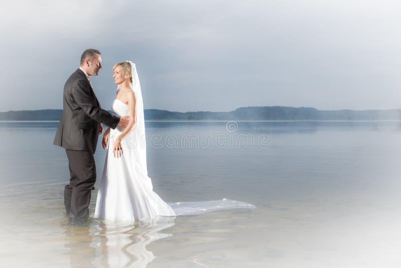 Glückliche junge Paare, die in einem See stehen lizenzfreie stockfotos