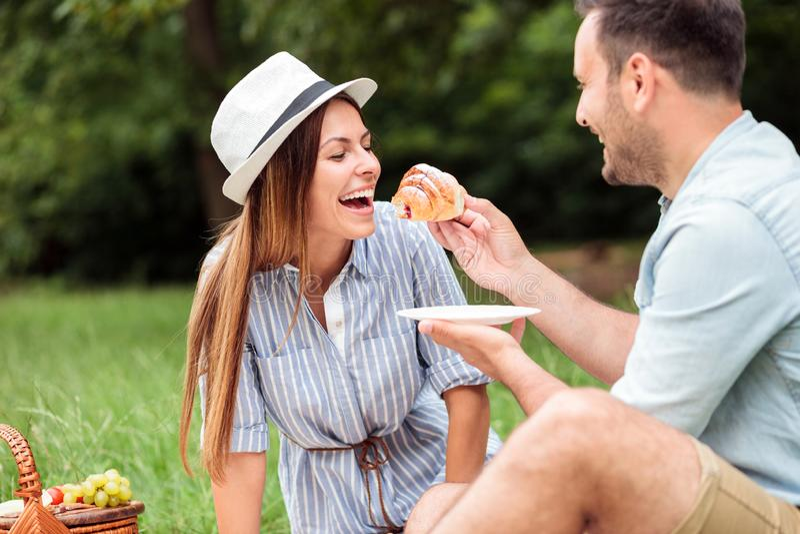 Glückliche junge Paare, die entspannendes im Park frühstücken, Hörnchen essen und Kaffee trinken stockbild