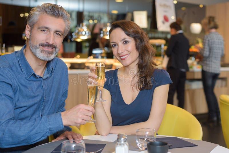 Glückliche junge Paare, die Geburtstag mit Champagner am Restaurant feiern lizenzfreies stockfoto