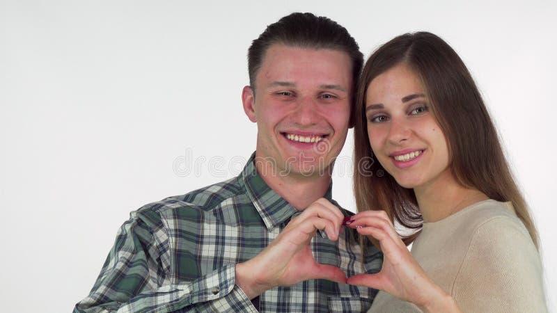 Glückliche junge Paare, die Herz mit ihren Händen, nett lächelnd bilden stockbild