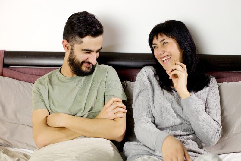 Glückliche junge Paare, die im Bett glücklich lächeln stockbilder