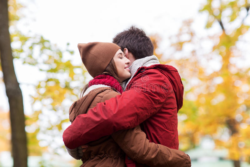 Glückliche junge Paare, die im Herbstpark umarmen lizenzfreie stockfotos