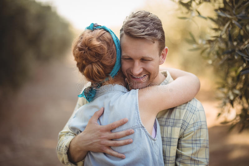 Glückliche junge Paare, die am olivgrünen Bauernhof umfassen lizenzfreies stockfoto