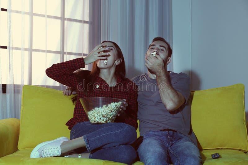 Glückliche junge Paare, die Popcorn beim Fernsehen essen stockfotos