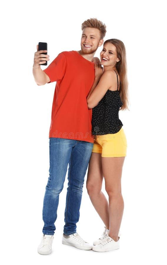 Glückliche junge Paare, die selfie auf Weiß nehmen lizenzfreie stockbilder