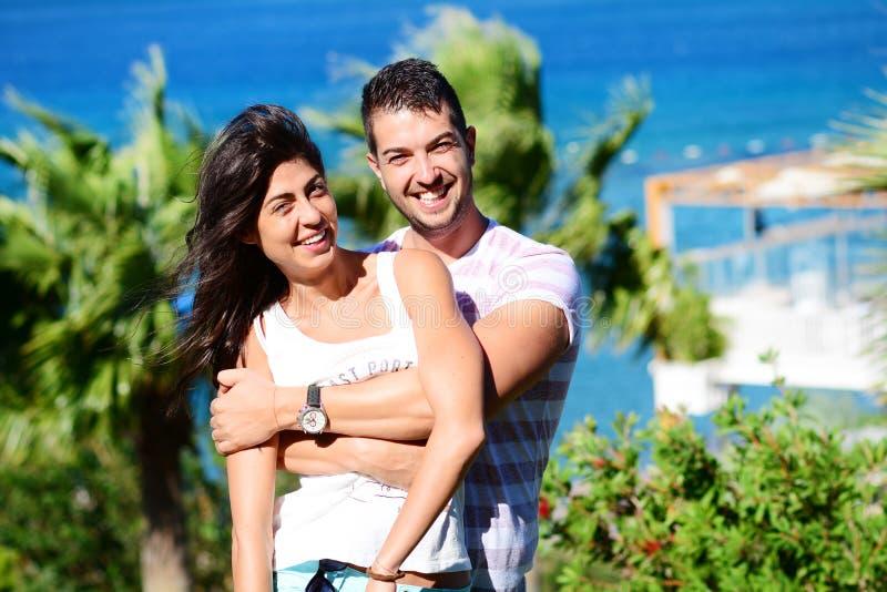Glückliche junge Paare, die Spaß auf einem Seehintergrund haben lizenzfreie stockbilder