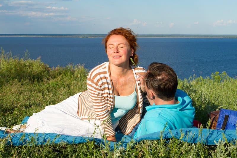 Glückliche junge Paare, die Spaß draußen und das Lächeln haben Schöne Paare, die auf Strand am Abend legen stockfotografie