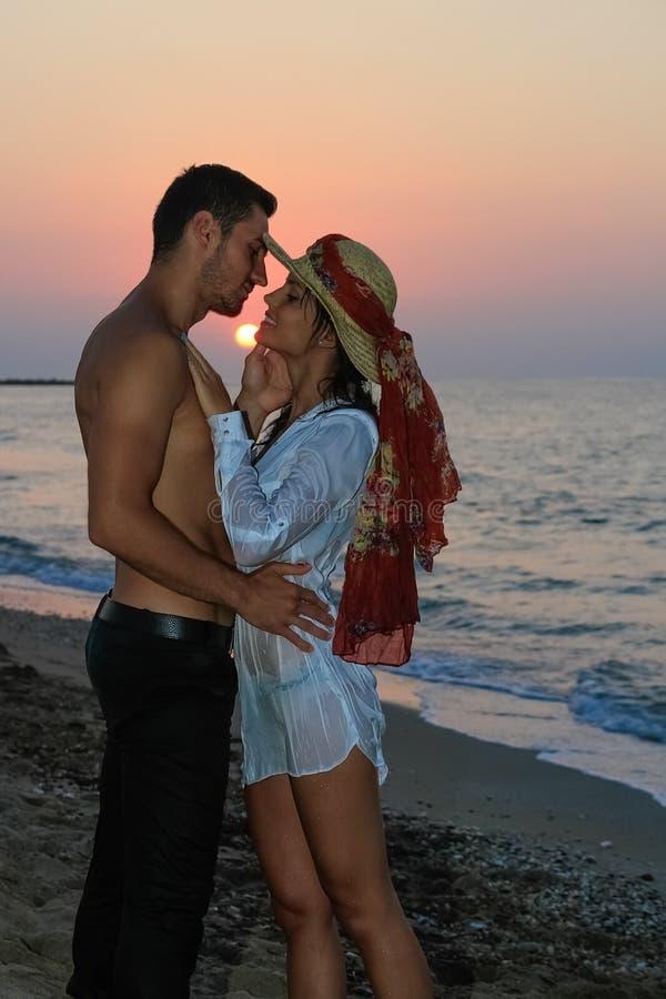 Glückliche junge Paare, die am Strand an der Dämmerung küssen lizenzfreie stockfotografie