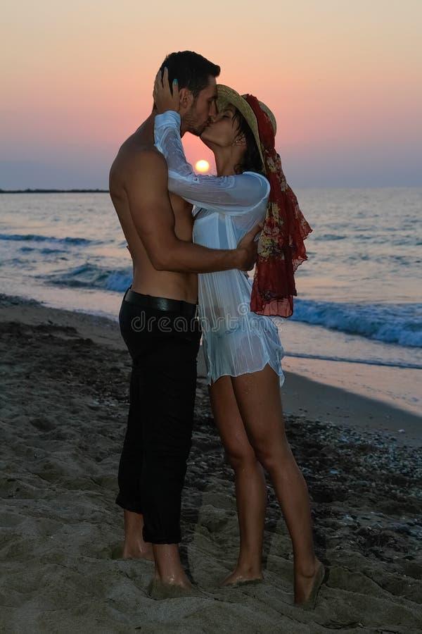 Glückliche junge Paare, die am Strand an der Dämmerung küssen lizenzfreies stockfoto