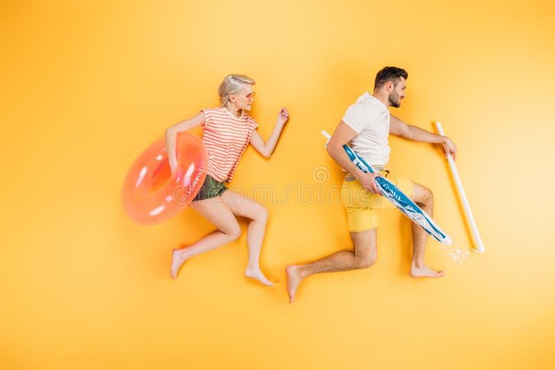 glückliche junge Paare, die Strandschirm und Schwimmring auf Gelb, Sommer halten lizenzfreies stockfoto