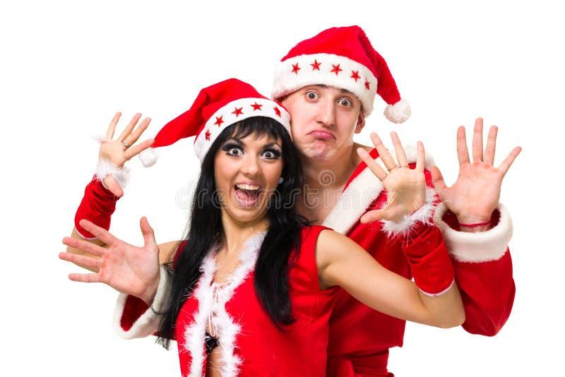 Glückliche junge Paare, die Weihnachtsmann-Kleidung tragen lizenzfreie stockfotos