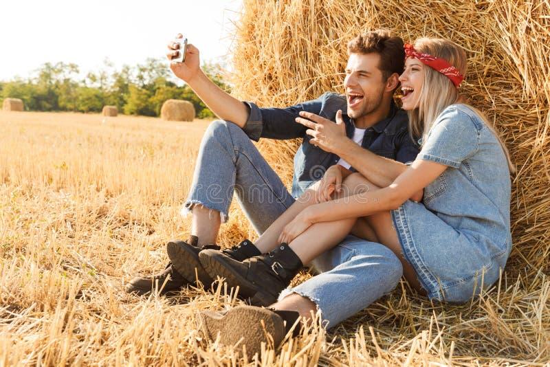 Glückliche junge Paare, die am Weizenfeld sitzen lizenzfreies stockfoto