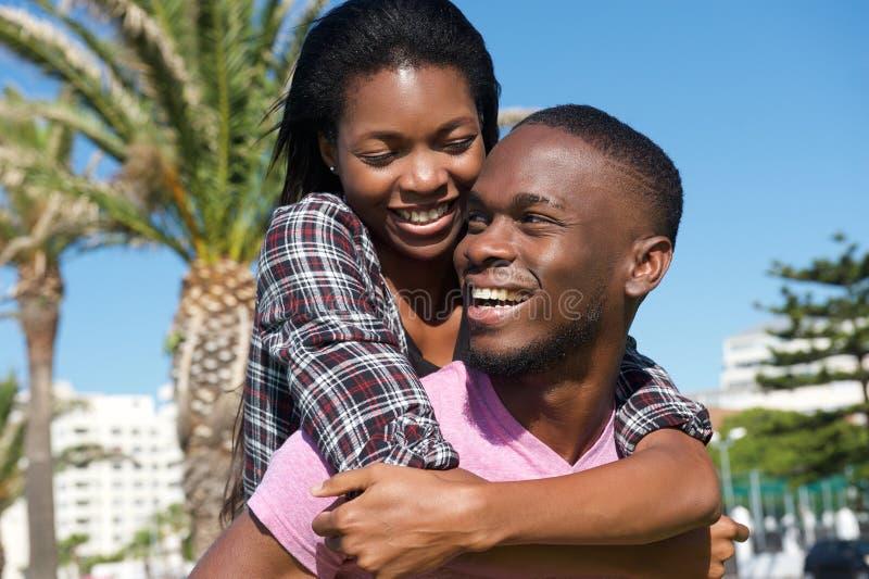 Glückliche junge Paare, die zusammen draußen lachen stockbild