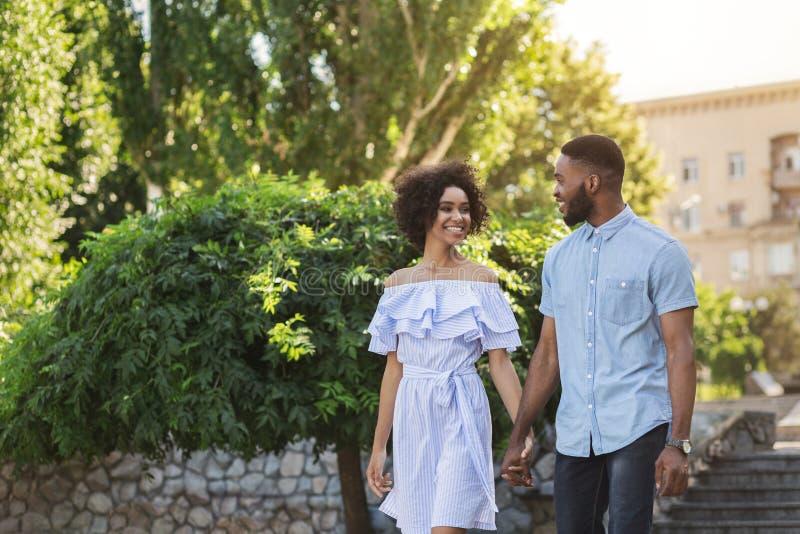 Glückliche junge Paare, die zusammen in Park gehen lizenzfreie stockfotografie