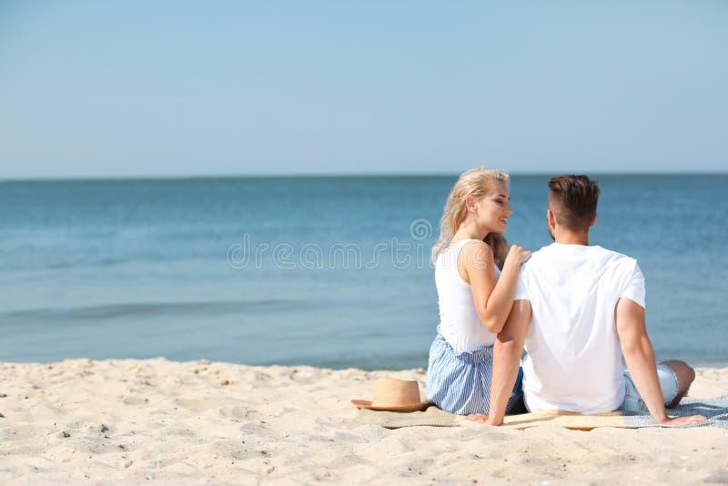 Glückliche junge Paare, die zusammen am Strand sitzen lizenzfreies stockfoto