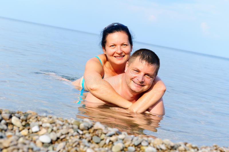 Glückliche junge Paare im Meer lizenzfreies stockbild
