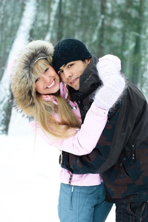 Glückliche junge Paare im Winterpark lizenzfreies stockbild