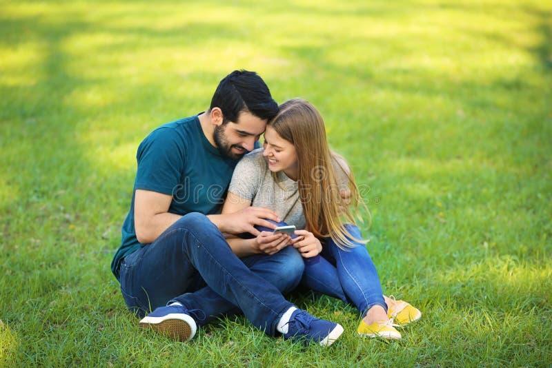 Glückliche junge Paare mit dem Handy, der auf grünem Gras im Park sitzt lizenzfreies stockbild