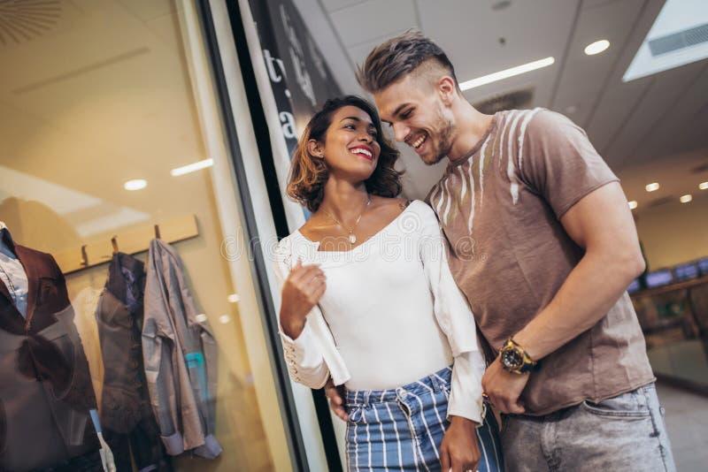 Glückliche junge Paare mit den Einkaufstaschen, die in Mall gehen stockfotografie