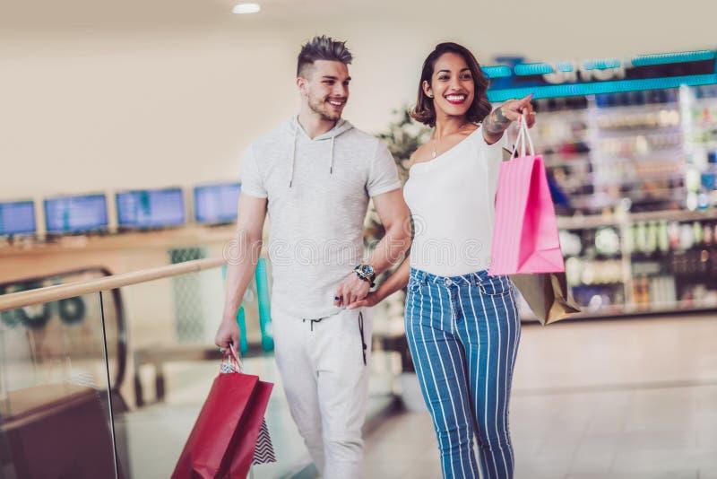Glückliche junge Paare mit den Einkaufstaschen, die in Mall gehen stockfoto