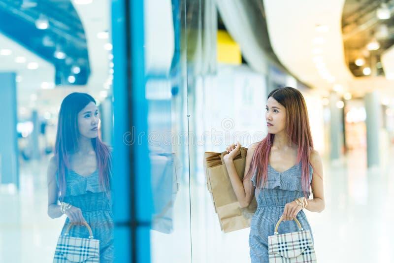 Glückliche junge Paare mit den Einkaufstaschen, die in mallConsumerism gehen stockfotos