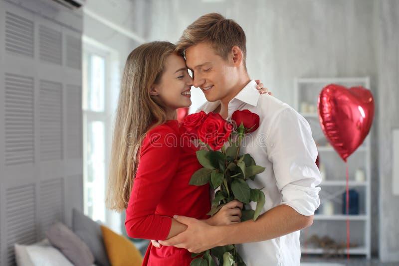 Glückliche junge Paare mit den roten Rosen, die zu Hause umarmen lizenzfreies stockfoto