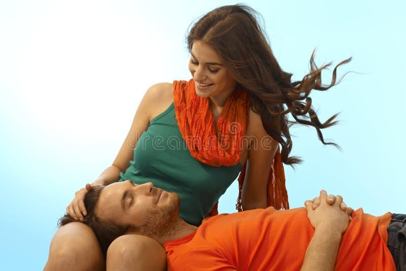 Glückliche junge Paare mit Mann im Schoss der Freundin lizenzfreie stockfotografie