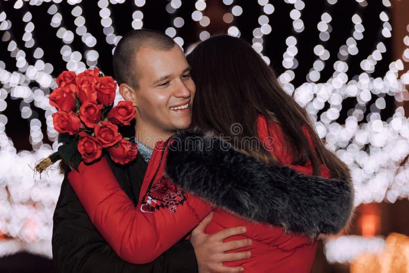 Glückliche junge Paare mit Rosenblumenstrauß auf einem Datum stockbild
