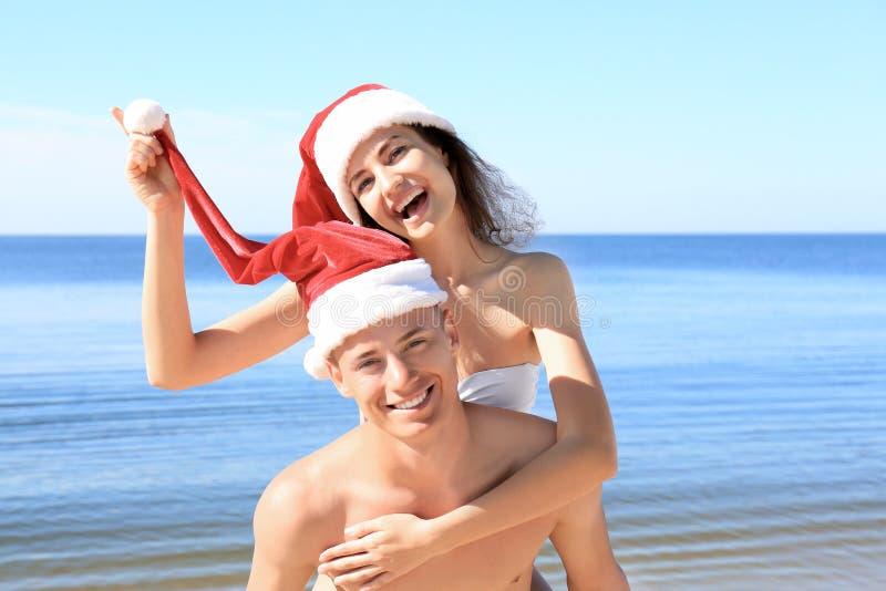Glückliche junge Paare in Sankt-Hüten auf Meer setzen auf den Strand lizenzfreie stockbilder
