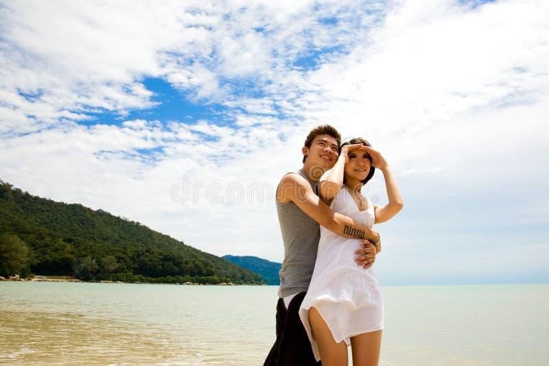 Glückliche junge Paare am Strand stockbilder