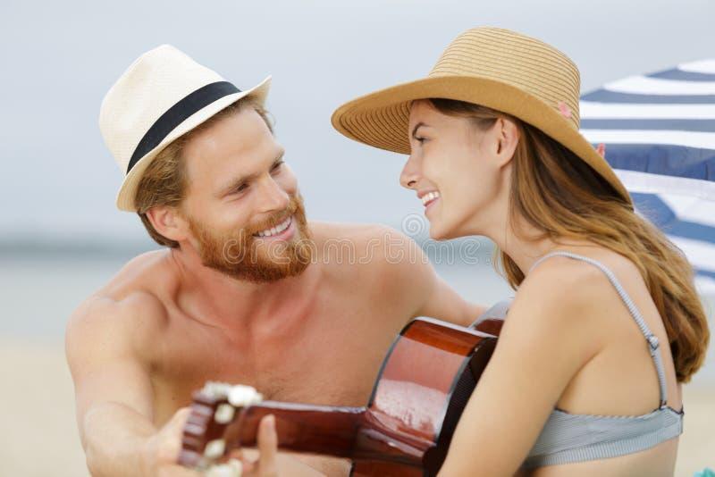Glückliche junge Paare am Strand, der Gitarre spielt lizenzfreies stockbild