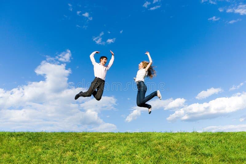 Glückliche junge Paare - Team springt in den Himmel lizenzfreies stockfoto