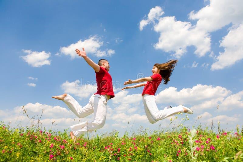 Glückliche junge Paare - Team springt in Himmel lizenzfreie stockbilder