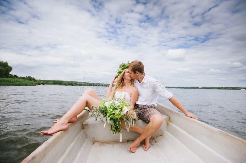 Glückliche junge Paare umarmen das Sitzen in einem Boot auf dem See- und Himmelhintergrund lizenzfreie stockbilder