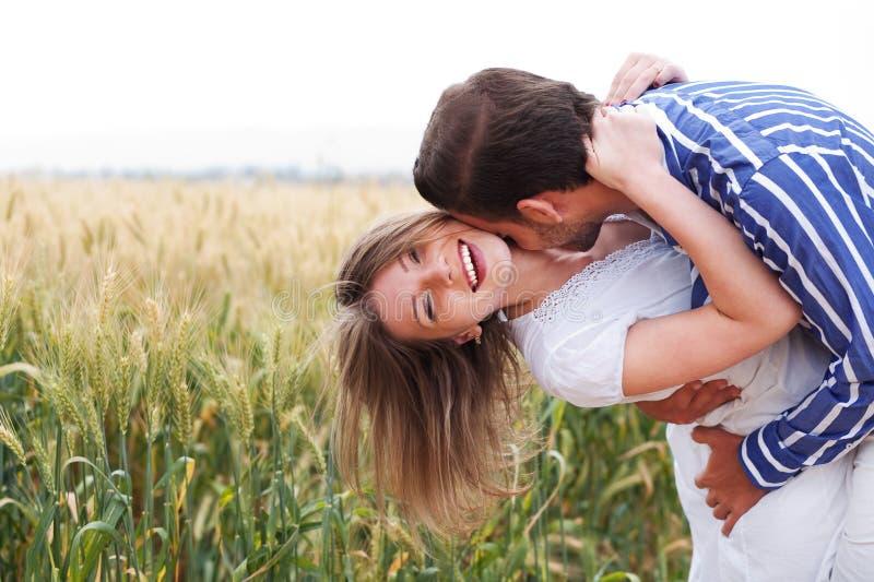 Glückliche junge Paare umarmendes und küssendes eachother lizenzfreies stockbild