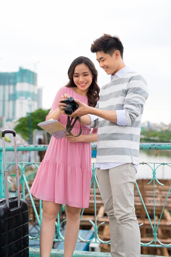 Glückliche junge Paare von den Reisenden, die Karte in den Händen halten stockfoto