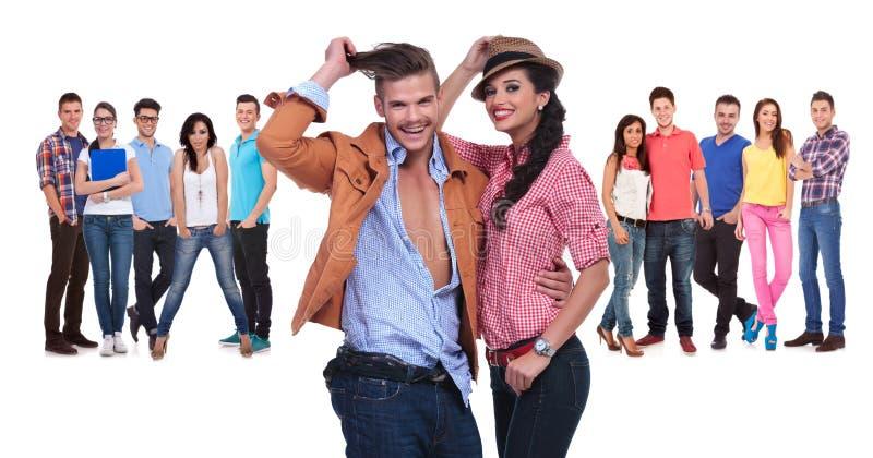 Glückliche junge Paare vor einem großen Team von zufälligen Leuten stockbild