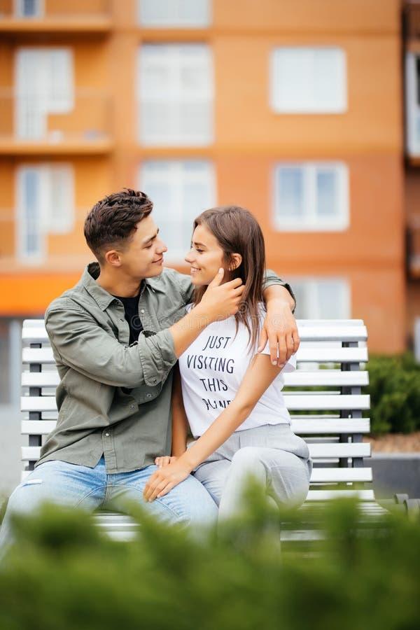 Glückliche junge Paarjugendliche sitzen auf der Bankstadt am sonnigen Tag des Sommers stockfotos
