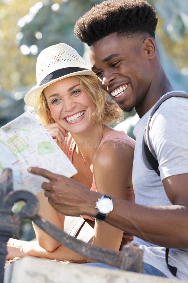 Glückliche junge Paarstellung mit Plan lizenzfreie stockbilder