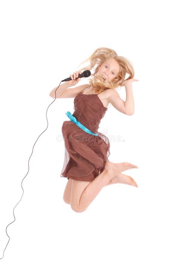 Glückliche junge schöne Jugendliche, die mit MICR springt und singt lizenzfreie stockbilder