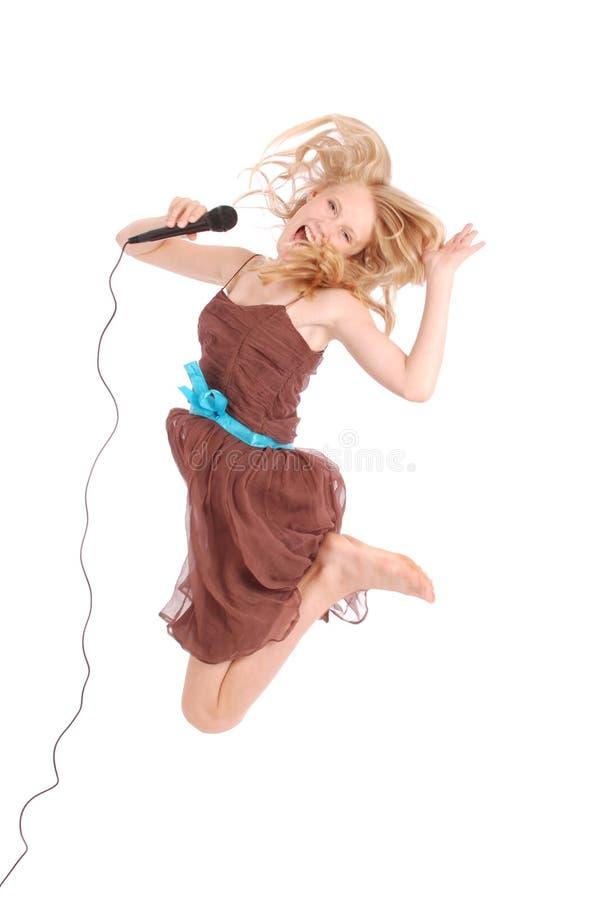Glückliche junge schöne Jugendliche, die mit MICR springt und singt lizenzfreies stockbild