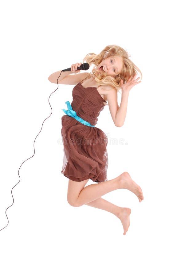 Glückliche junge schöne Jugendliche, die mit MICR springt und singt stockfotografie