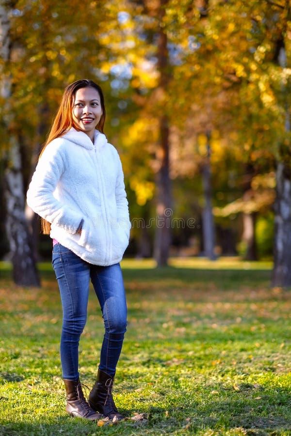 Glückliche junge Schönheit im Herbstpark am sonnigen Tag, junge Frau im weißen Mantel während des Sonnenuntergangs im Park stockfotografie