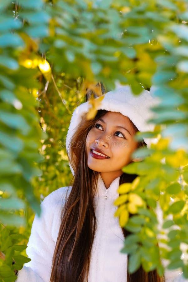 Glückliche junge Schönheit im Herbstpark am sonnigen Tag, junge Frau im weißen Mantel während des Sonnenuntergangs im Park lizenzfreies stockbild