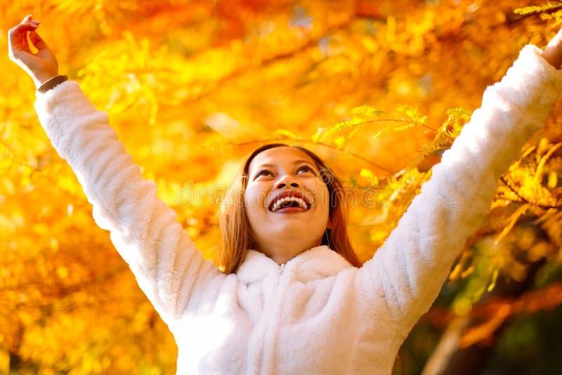 Glückliche junge Schönheit im Herbstpark am sonnigen Tag, junge Frau im weißen Mantel während des Sonnenuntergangs im Park lizenzfreie stockbilder