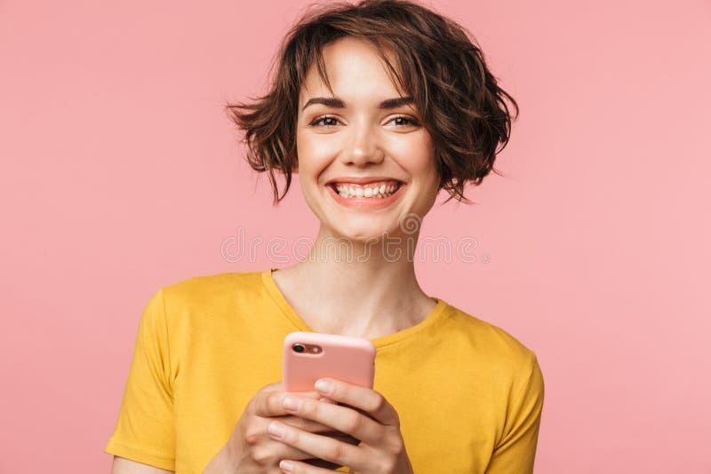 Glückliche junge Schönheitsaufstellung lokalisiert über rosa Wandhintergrund unter Verwendung des Handys stockbilder
