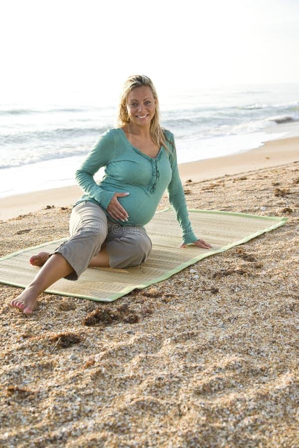 Glückliche junge schwangere Frau, die auf Matte am Strand sitzt lizenzfreie stockfotografie