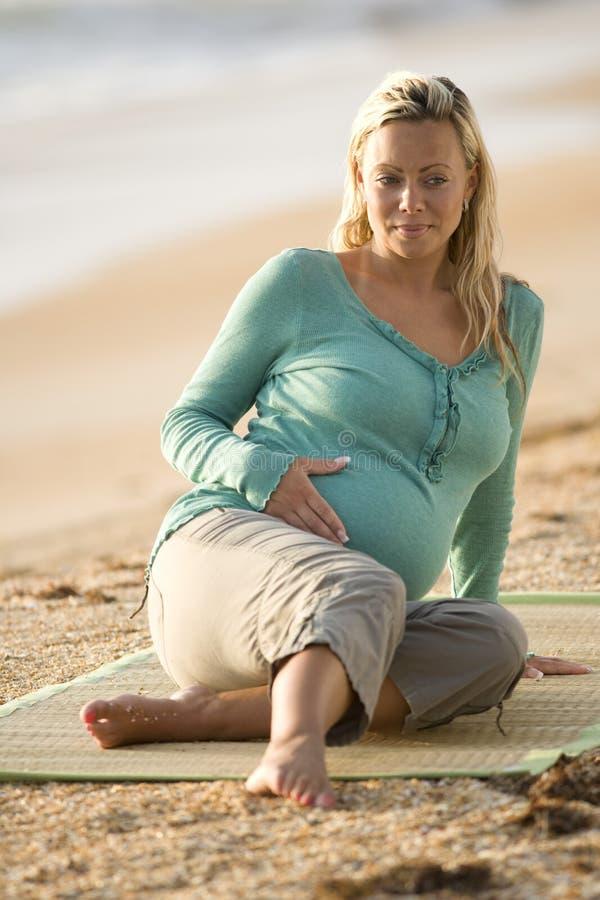 Glückliche junge schwangere Frau, die auf Matte am Strand sitzt stockfotografie