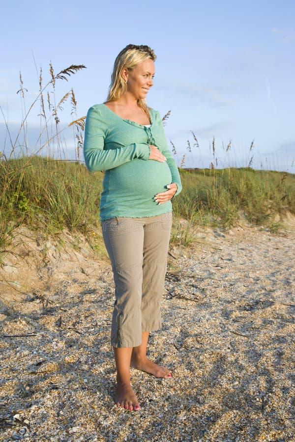 Glückliche junge schwangere Frau, die auf Strand steht stockfotografie